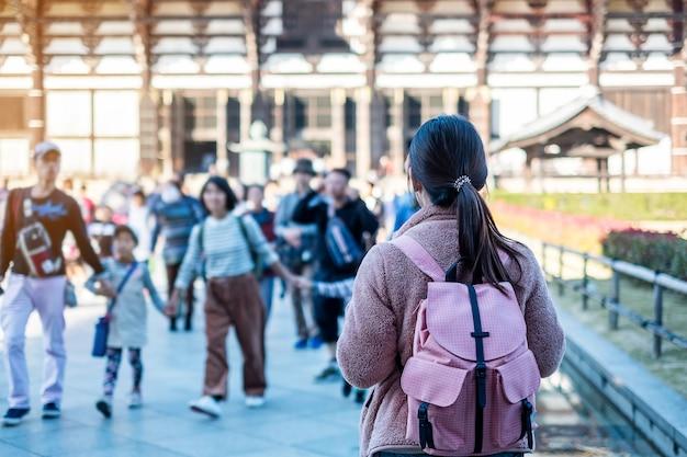 Jonge vrouw die bij todaiji-tempel, gelukkig aziatisch reizigersbezoek reizen in nara dichtbij osaka. landmark en populair voor toeristische attracties in nara, japan. azië reizen concept