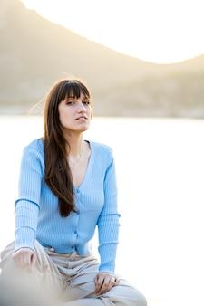 Jonge vrouw die bij zonsondergang voor de zee zit en naar de camera kijkt