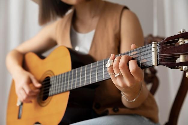 Jonge vrouw die binnen gitaar speelt