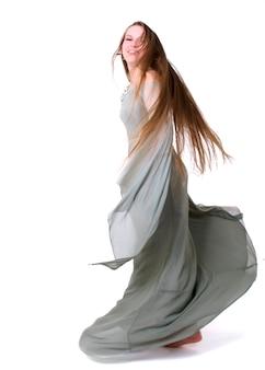 Jonge vrouw die binnen tegen witte achtergrond danst