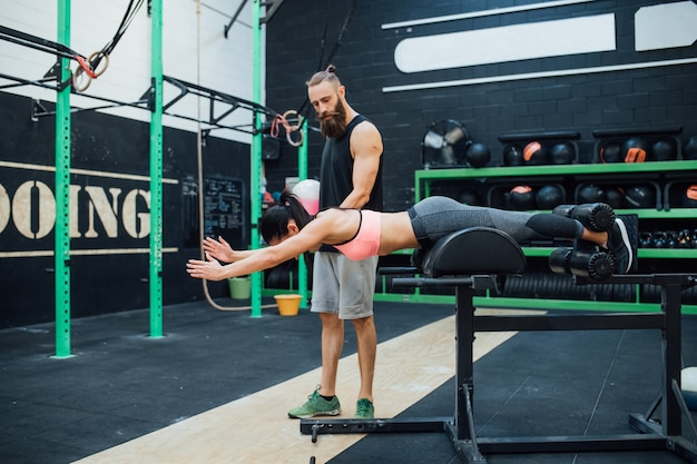 Jonge vrouw die binnengymnastiek met persoonlijke trainer uitoefent