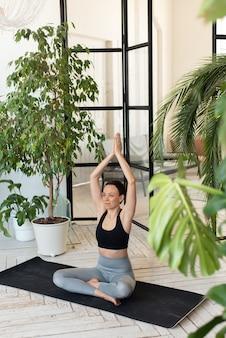 Jonge vrouw die binnenshuis mediteert. pose jonge vrouw lachend voor de camera, zittend in de lotushouding. ontspanning en meditatie thuis tussen de planten.