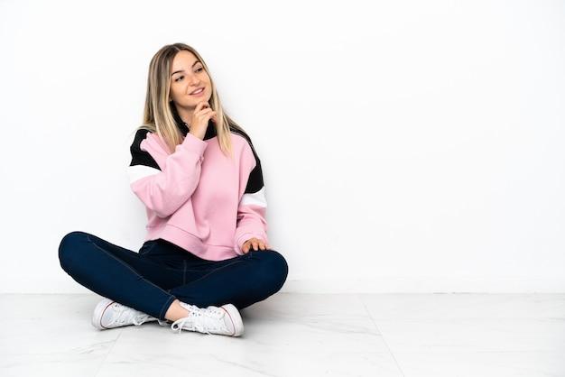 Jonge vrouw die binnenshuis op de grond zit en naar de zijkant kijkt en glimlacht