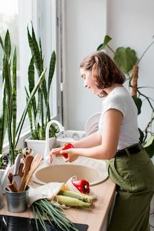 Jonge vrouw die biologische groenten schoonmaakt