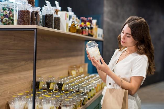 Jonge vrouw die bioproducten winkelt