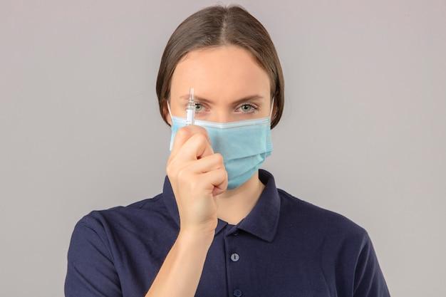 Jonge vrouw die blauw poloshirt in beschermend medisch masker draagt dat een ampul met een vaccin houdt dat camera met ernstig gezicht bekijkt dat zich op geïsoleerde grijze achtergrond bevindt