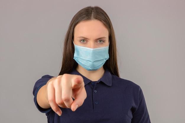 Jonge vrouw die blauw poloshirt in beschermend medisch masker draagt dat vinger richt aan camera met ernstig gezicht dat zich op lichtgrijze achtergrond bevindt