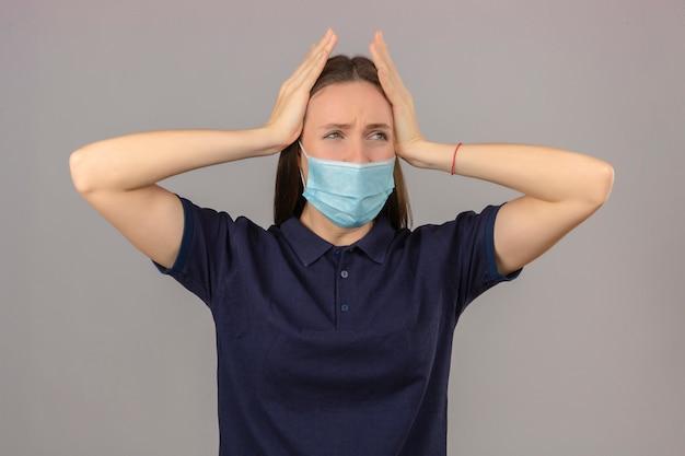 Jonge vrouw die blauw poloshirt in beschermend medisch masker draagt wat betreft hoofd die sterke hoofdpijn voelen die op lichtgrijze achtergrond wordt geïsoleerd