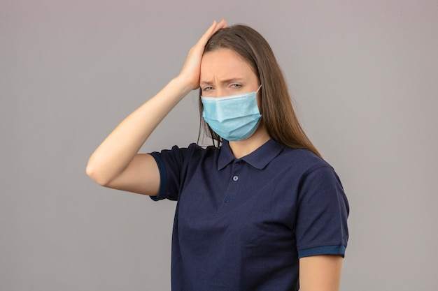 Jonge vrouw die blauw poloshirt in beschermend medisch masker draagt wat betreft hoofdgevoelend hoofdpijn die op lichtgrijze achtergrond wordt geïsoleerd