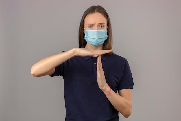 Jonge vrouw die blauw poloshirt in beschermend medisch masker dragen die het gebaar van de tijd uit hand tonen die zich op lichtgrijze geïsoleerde achtergrond bevinden