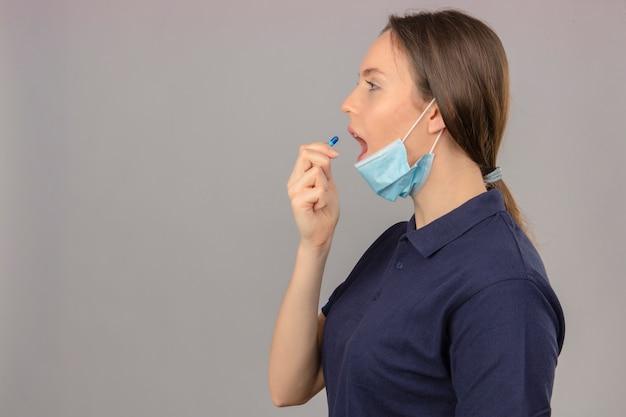 Jonge vrouw die blauw poloshirt in beschermend medisch masker met open mond draagt die een pil op lichtgrijze achtergrond neemt