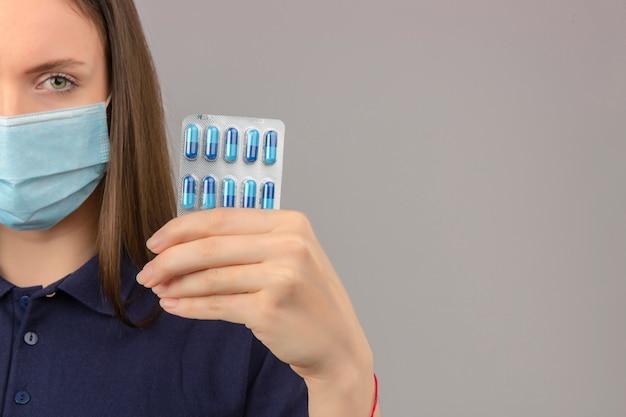 Jonge vrouw die blauw poloshirt in medisch masker dragen die ernstig de blaar van de cameraholding met in hand pillen bekijken op lichtgrijze geïsoleerde achtergrond