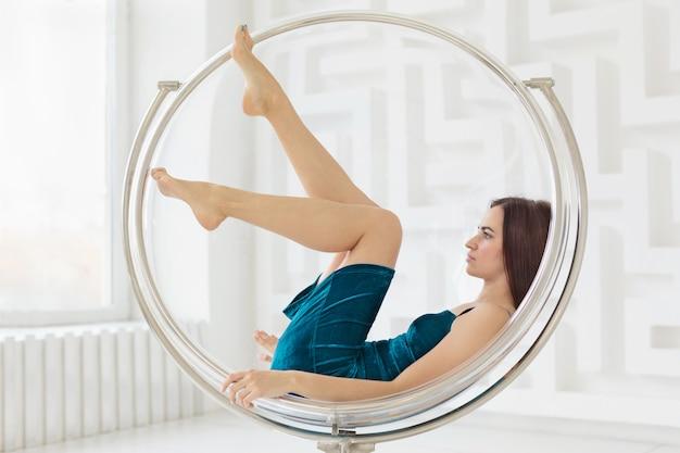 Jonge vrouw die blauwe kleding draagt die in ronde glasstoel ligt in witte ruimte. zijaanzicht
