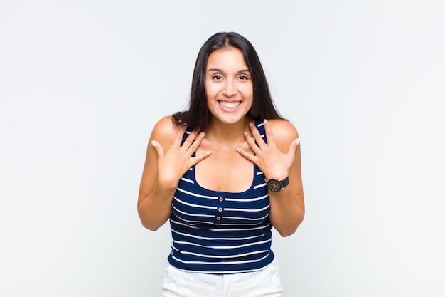 Jonge vrouw die blij, verrast, trots en opgewonden kijkt, wijzend naar zichzelf