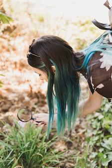 Jonge vrouw die bloemen door vergrootglas kijkt