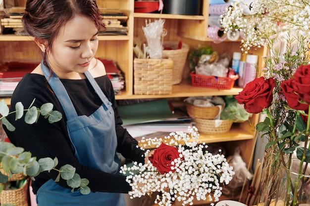 Jonge vrouw die bloemen in boeket schikken