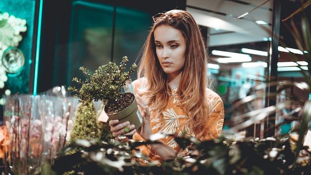 Jonge vrouw die bloemen in een pot bij een tuincentrum koopt