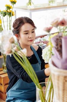 Jonge vrouw die bloemen in opslag schikken