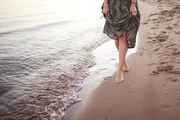 Jonge vrouw die blootvoets op brandingslijn, benen en rok dicht omhoog lopen