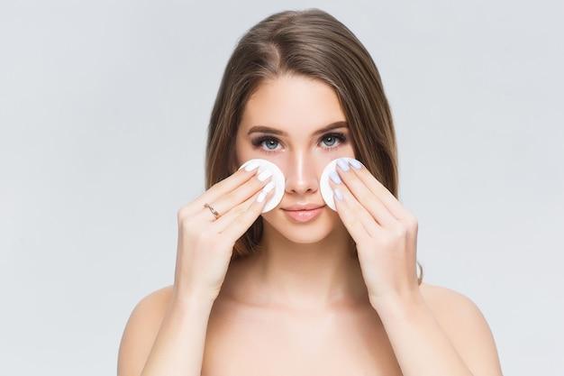 Jonge vrouw die blush op haar gezicht aanbrengt met poederdons