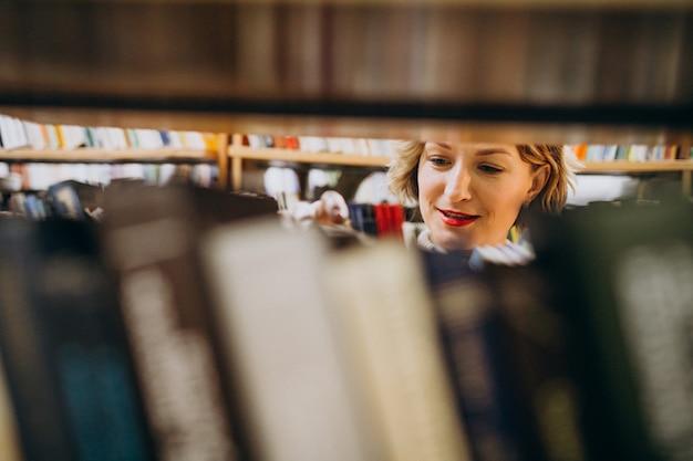 Jonge vrouw die boek kiest bij de bibliotheek