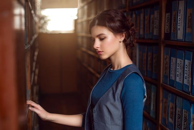 Jonge vrouw die boek uit bibliotheekplank selecteert.
