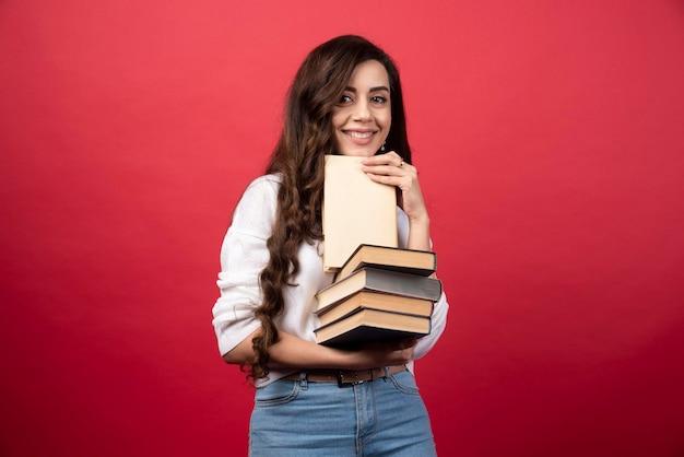 Jonge vrouw die boeken draagt en op een rode achtergrond glimlacht. hoge kwaliteit foto