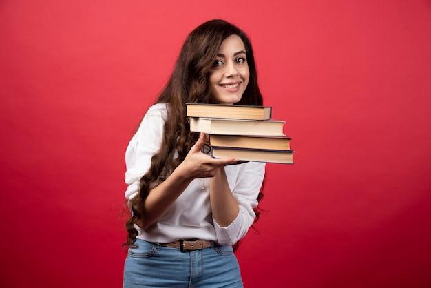 Jonge vrouw die boeken op een rode achtergrond draagt. hoge kwaliteit foto