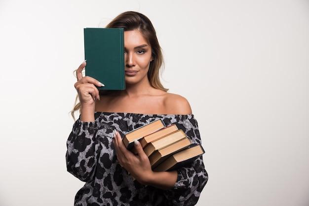 Jonge vrouw die boeken op witte muur toont.