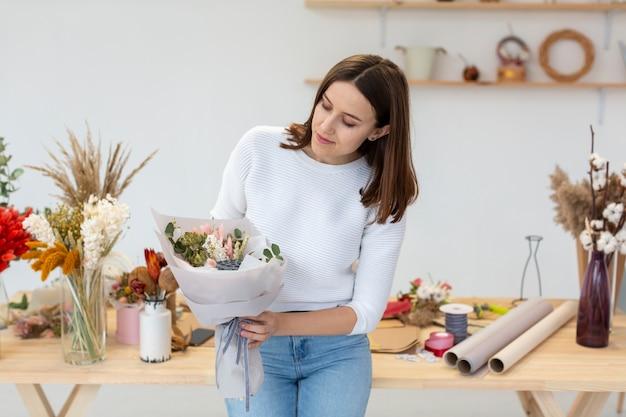Jonge vrouw die boeket van bloemen bekijkt