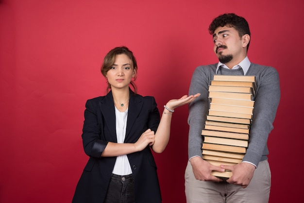 Jonge vrouw die boos wordt op de man die een stapel boeken bij zich heeft