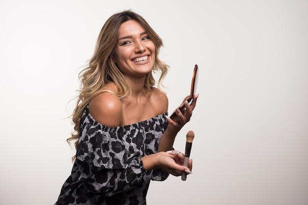 Jonge vrouw die bronzer op witte muur toepast.