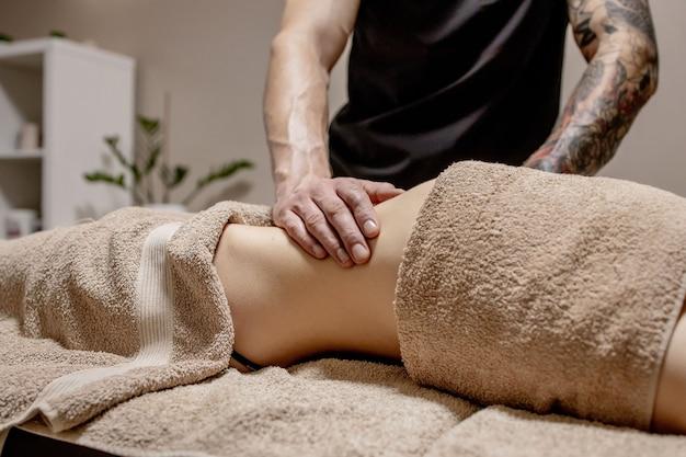 Jonge vrouw die buikmassage heeft. masseur maakt massage voor maag.