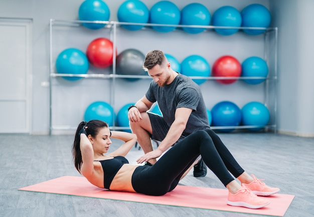 Jonge vrouw die buikoefeningen doet met hulp haar coach een mat in gymnastiek.