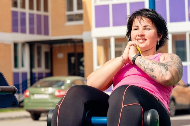 Jonge vrouw die buikspieroefeningen uitvoert met behulp van een zitbank in de buitenlucht