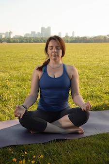 Jonge vrouw die buiten op yogamat mediteert