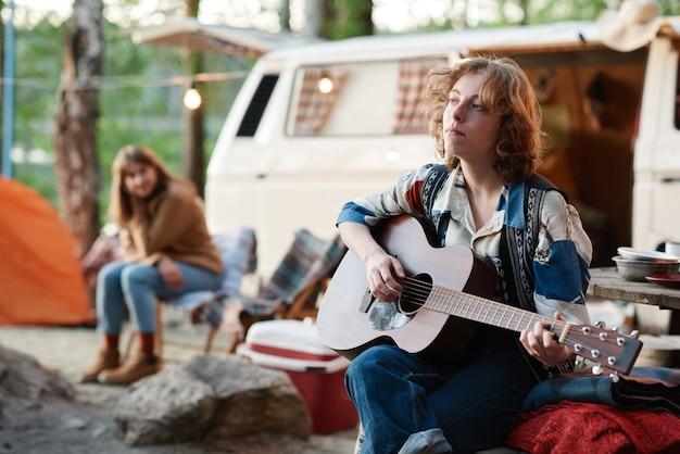 Jonge vrouw die buiten zit en gitaar speelt tijdens het kamperen in het bos