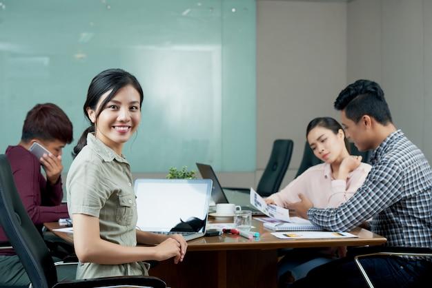 Jonge vrouw die camera bekijkt die van de afdelingsvergadering met collega's wordt afgeleid
