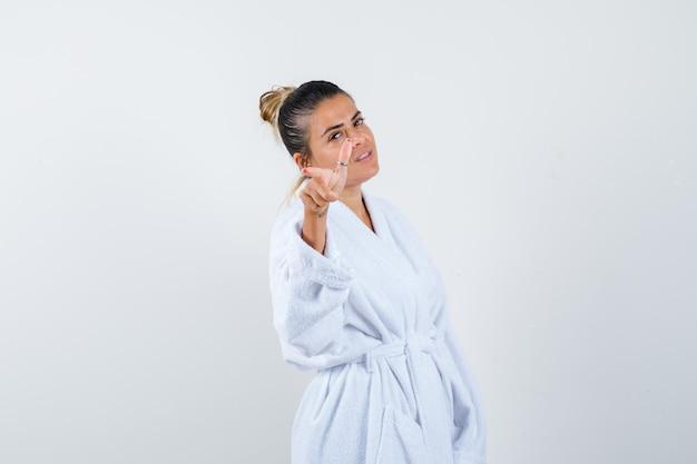 Jonge vrouw die camera in badjas richt en er gelukkig uitziet