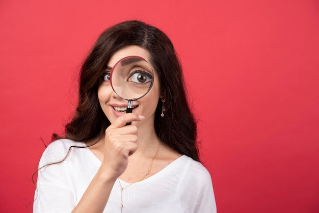 Jonge vrouw die camera met vergrootglas bekijkt. hoge kwaliteit foto