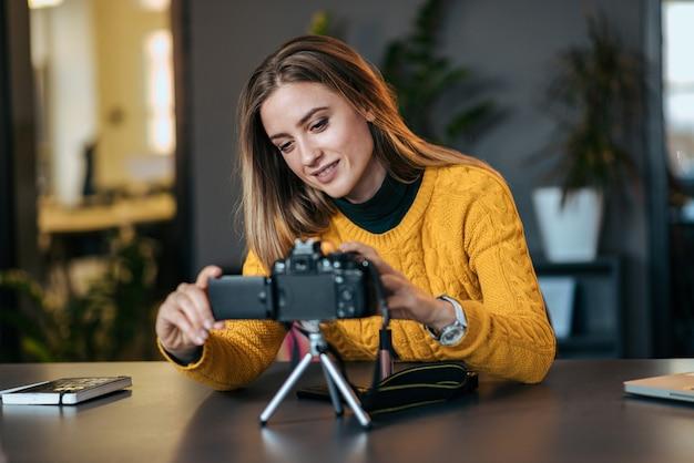 Jonge vrouw die camera voor vlogging voorbereidt.