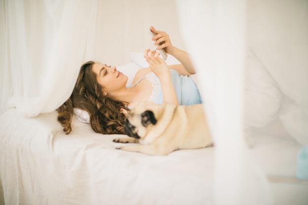 Jonge vrouw die cellphone in bed gebruikt. kleine pug hond ligt naast haar