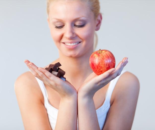Jonge vrouw die chocolade en appeldrank op chocolade en appel toont