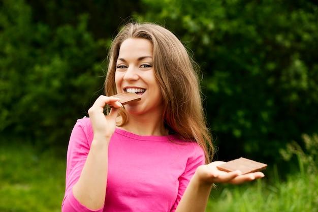 Jonge vrouw die chocolade in bos eet