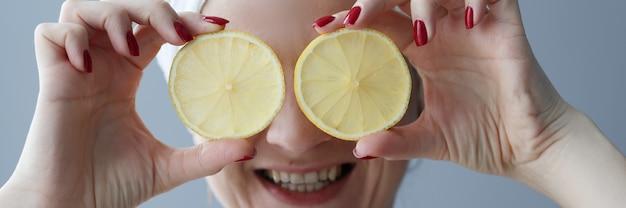 Jonge vrouw die citroenen voor haar ogen houdt