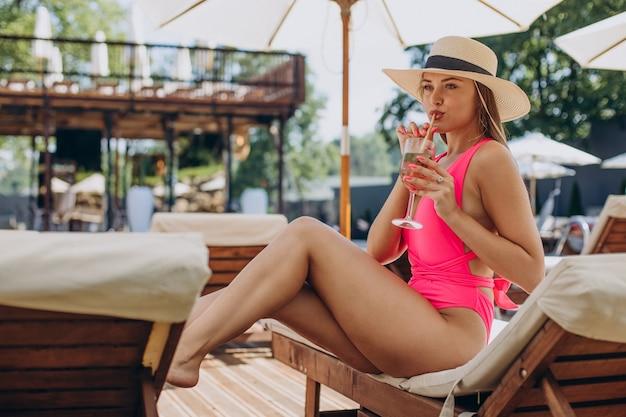 Jonge vrouw die cocktail drinkt en op zonnebank ligt