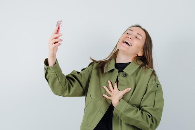 Jonge vrouw die compliment ontvangt tijdens videogesprek in groene jas en tevreden kijkt. vooraanzicht.