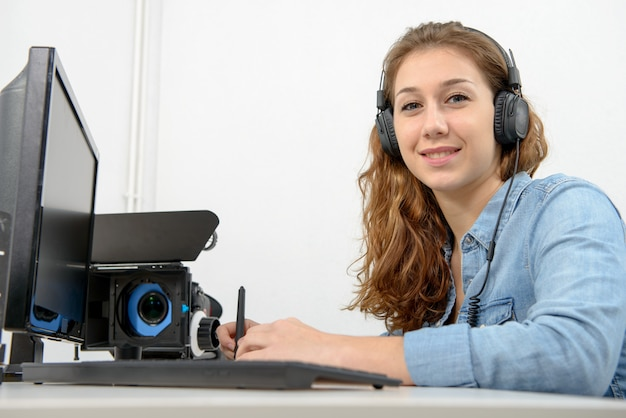 Jonge vrouw die computer voor videobewerking met behulp van