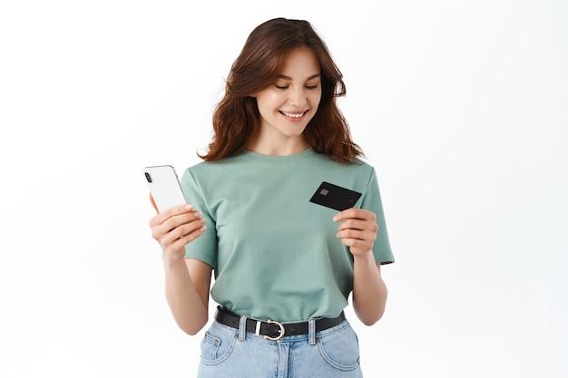 Jonge vrouw die creditcardnummer leest en online betaalt met smartphone, geld overmaakt, app voor mobiel bankieren gebruikt, tegen een witte muur staat