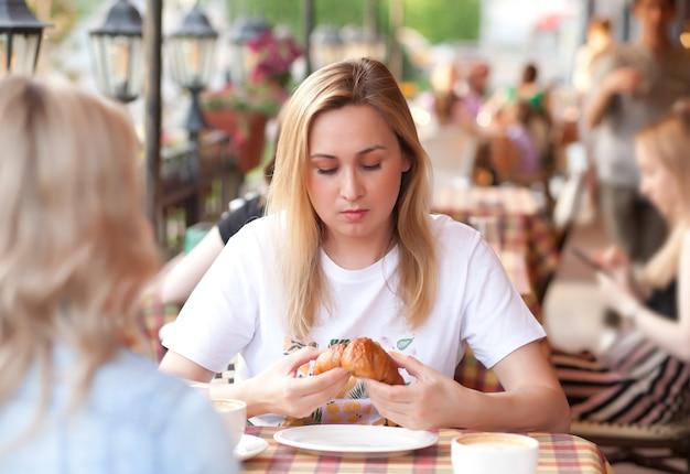 Jonge vrouw die croissant eet en koffie drinkt op een caféterras met vrienden